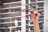 Hand write Under construction on blurred background of construction worker building on a scaffold — Stock Photo
