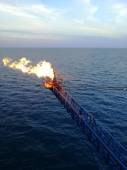 Flare boom nozzle and fire on offshore oil rig — Stock Photo