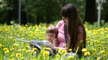 Young mother and her daughter read a children's book outdoors — Stock Video