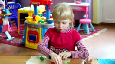 Girl in kindergarten deals with the modeling of the plasticine. She is very serious, focused and passionate about a favorite pastime. It brings her pleasure — Stock Video