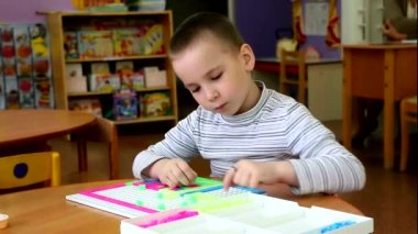 Boy in kindergarten closely engaged in a Board game. He's very serious, focused and passionate about a favorite pastime. It brings him pleasure. — Stock Video