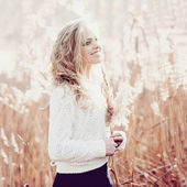 Portrait of a beautiful young blonde girl in a field in white pullover, smiling, concept beauty and health — Stock Photo