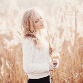 Portrait of a beautiful blonde girl in a field in white pullover, smiling with eyes closed, concept beauty and health — Stock Photo