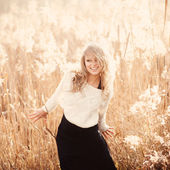 Portrait of a beautiful young blonde girl in a field in white pullover, smiling, concept of beauty and health — Stock Photo