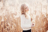 Portrait of a beautiful young blonde girl in a field in white pullover, smiling with eyes closed, concept beauty and health — Stock Photo