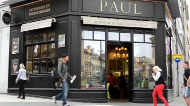 Paul Bakery exterior in the city - people walk on pavement — Stock Video
