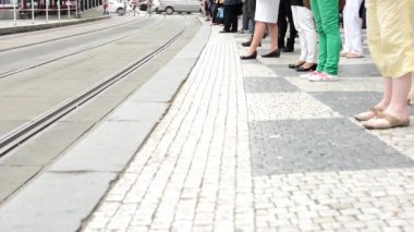 People wait at the tram stop - in the city - detail of legs - passing cars in the background — Stock Video