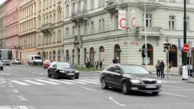 Urban street with passing cars and pedestrian crossing: people walking - buildings in the city in background - timelapse — Stock Video