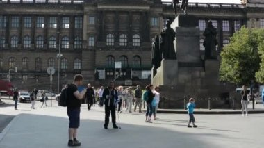 Wenceslas Square with people and passing cars - buildings and nature(trees and bushes) - National Museum with staue of Wenceslaus — Stock Video