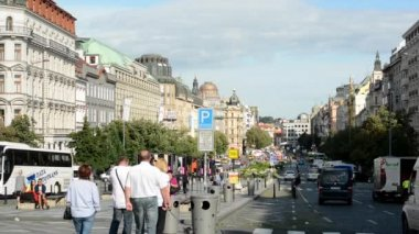Wenceslas Square with people and passing cars - buildings and nature(trees and bushes) - blue sky — Stock Video