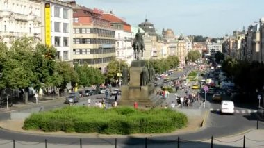 Wenceslas Square with people and passing cars - timelapse - buildings and nature(trees and bushes) - blue sky — Stock Video