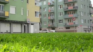 High rise block of flats with green grass a parked cars - slider move — Vidéo