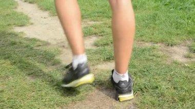 Man sports - running - detail of legs - man warming up and then start running - green grass — Stock Video