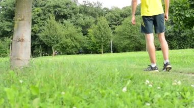 Man sports - running - man warming up and then start running - green grass with trees - other people in background — Stock Video