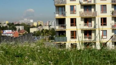 Green grass with city (buildings: high-rise block of flats) in the background - blue sky — Stock Video
