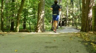 Man sports - running - forest: park (trees) - pathway - suns rays - slider — Stockvideo
