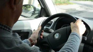 Old man(senior) drives a car - steering wheel — Stock Video