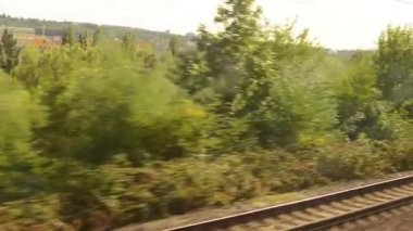 Moving train on the tracks - city (buildings) and trees - railway yard (rails) - motion (move) shot — Stock Video