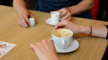 Young couple sit (man and woman) at the table with coffee - shot only on hands and coffee - soft blurred — Stock Video