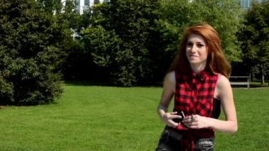 Young attractive woman is in the park - woman with cute smile - she holds smartphone in hands - nature — Stock Video