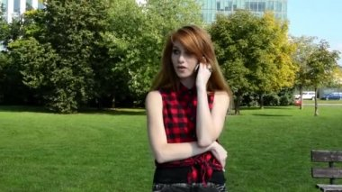 Young attractive woman is in park  - nature - woman telephone and smiles - nature — Stock Video
