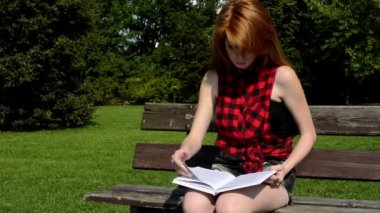 Young attractive woman sits on bech in the park - woman reads a book  - nature — Stock Video