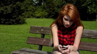 Young attractive woman sits on bech in the park and smiles - woman works on the smartphone (sms) - nature — Stock Video