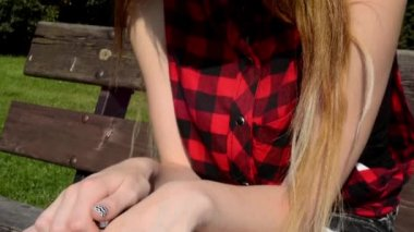 Young attractive woman sits on bech in the park - in her hand is crucifix (cross) - nature — Stock Video