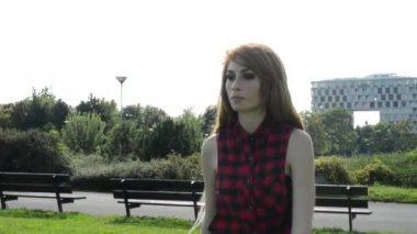 Junge attraktive frau geht in park - natur mit modernen gebäuden im hintergrund — Stockvideo