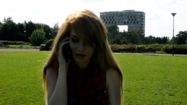 Young attractive woman goes in park  - nature with modern building in the background - woman telephone - nature — Stock Video