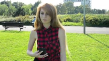 Young attractive woman goes in park and listens to music on smartphone - other people in the background with buildings and nature (tree and grass) — Stock Video