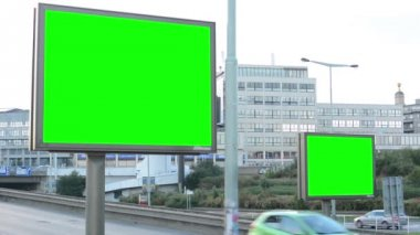 Two billboards in the city near road - green screen - building and passing cars in background — Vídeo Stock