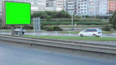 Billboard in the city near road - green screen - building and passing cars in background — Vídeo Stock