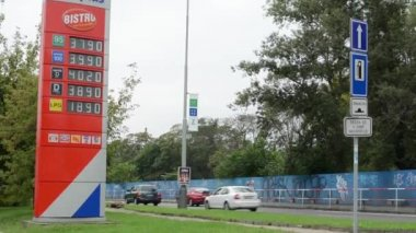 Fuel station - passing cars - trees and grass - information panel with fuel prices — Stock Video