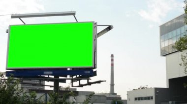 Billboard in the city - green screen - buildings(factory) in the background - smokestack — Stockvideo