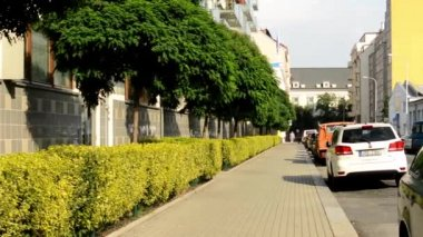 City - urban street with parked cars - flats (apartments) - sunlight - pavement — Stockvideo