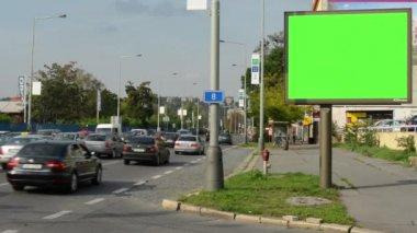 Panneau d'affichage dans la ville près de routes et de bâtiments personnes - écran vert - avec des voitures — Vidéo