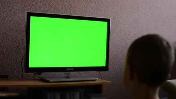 Child (young boy) watches television - green screen