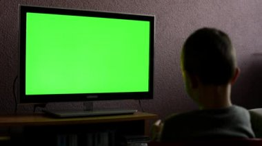 Child (young boy) watches television - child plays with a TV controller - green screen — Stock Video