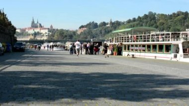 Boats on the river in quay (Vltava) - people get on - city (Prague Castle - Hradcany) in background - walking people - waterfront  - sunny (blue sky) — Stock Video