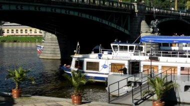 лодки на реке в причале (влтава) - мосте - автомобили и деревья - люди, идущие - береговой линии - солнечный (синее небо) — Стоковое видео