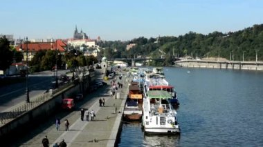 Boats on the river in quay (Vltava) - city (buildings) in background - Prague Castle (Hradcany) - sunny (blue sky) - cars and trees - walking people - waterfront — Stock Video