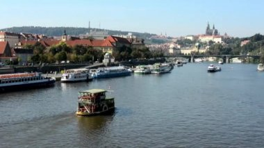 Boats on the river (Vltava) - city (buildings) in background - Prague Castle (Hradcany) - sunny (blue sky) - cars and trees — Stock Video
