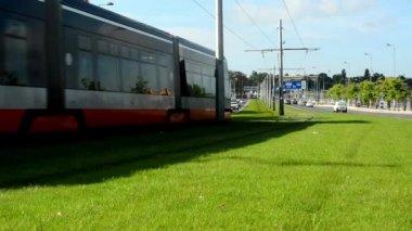 City: urban street - passing tram - cars - buildings - green grass — Stock Video