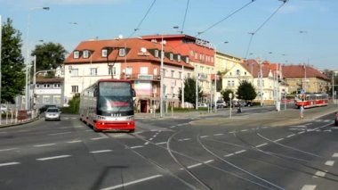 Passing trams on the urban street - cars - buildings - nature (trees) - sunny — Stock Video