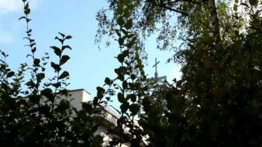 Nature (trees) - modern church (tower with a crucifix) - blue sky — Stock Video