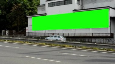 Billboard on a building - green screen - street - road with cars - nature (trees — Stockvideo
