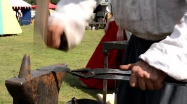 Blacksmith works in the forge at the exhibition - fire and smoke - people — Stock Video