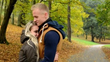 Woman cuddles to men - young model happy couple in love - autumn park (nature) — Stock Video