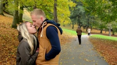 Young model couple in love plays - autumn park (nature) - happy couple kiss and talk - people in autumn park — Stock Video